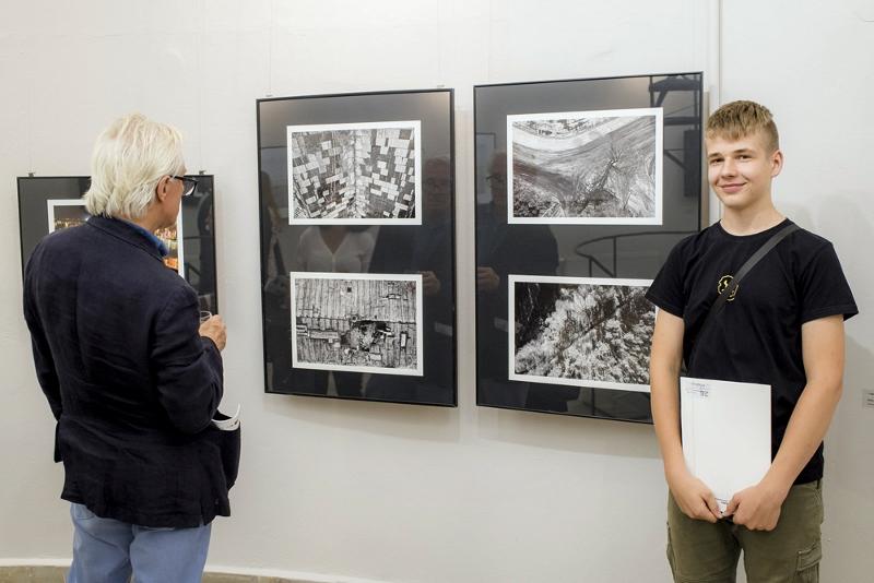 Uśmiechnięty Piotr Kosmala stoi przy nagrodzonych pracach
