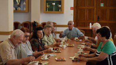 Samorządowi Seniorzy siedzą przy kawie i rozmawiają